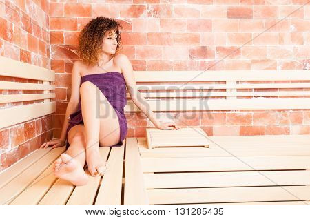 Beautiful Curly Woman Wearing Purple Towel And Relaxing