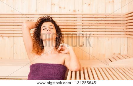 Young Curly Woman In A Sauna Relaxing With Closed Eyes