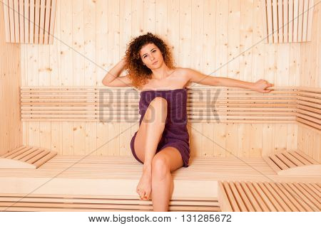 Pretty Woman Sitting Relaxed In A Wooden Sauna