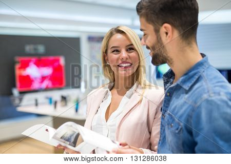 Couple looking catalogue in a tv store.