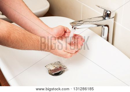 Close-up Of Man Washing Hands Under Stream Water