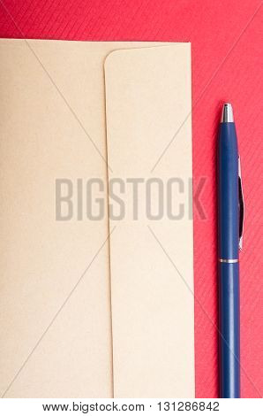 Close-up Of Brown Envelop And Pen Isolated On Red Background