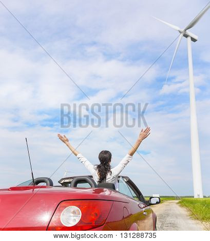 Woman in a red cabriolet in a field with wind power, raises her arms up. Travel or freedom concept.