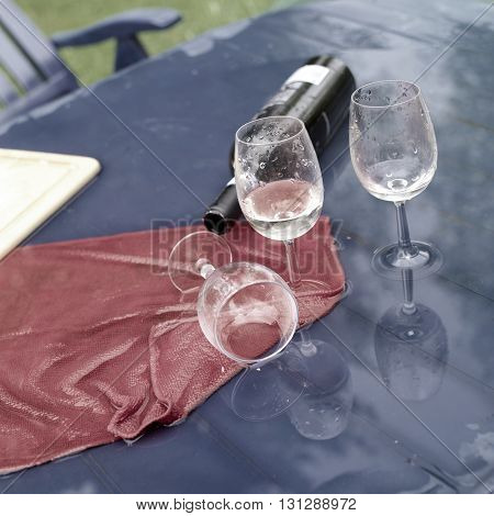 Overturned wine glasses and bottle on the wet table concept of a hangover and party end. Outdoor square shot