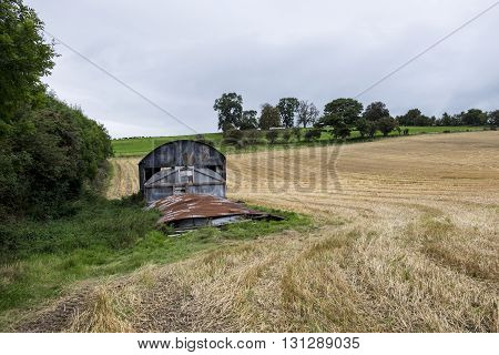 Rusty old barn in recently harvested field