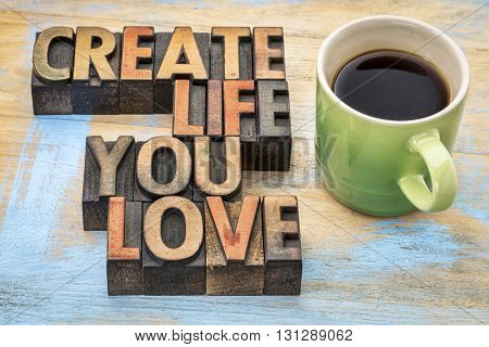 create life you love  - inspirational text in vintage letterpress wood type blocks stained by color inks with a cup of coffee