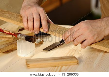 Carpenter gluing pieces of wood together closeup