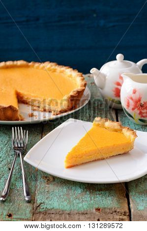 Homemade bright pumpkin pie and teaware on shabby wooden table vertical