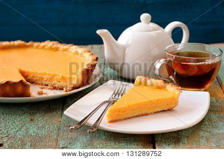 Homemade tasty pumpkin pie and black tea on shabby wooden table horizontal