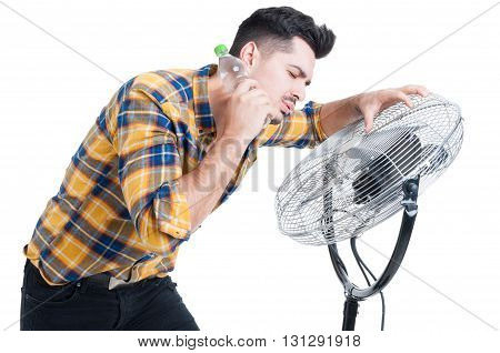 Sweaty And Thirsty Man Standing Near Fan And Cooling Off