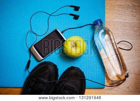 Sport equipment. Sneakers water apple smartphone and earphones on yoga mat