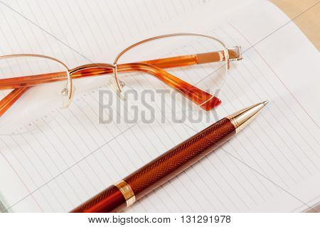 Daily planner with glasses and pen on the table. Selective focus