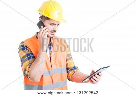 Multitasking Concept With Young Constructor Holding A Tablet And Cellphone