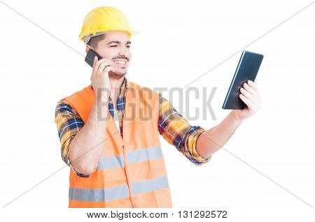 Male Constructor With Modern Tablet Using Cell Phone And Smiling