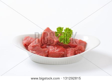 bowl of diced raw beef meat on white background