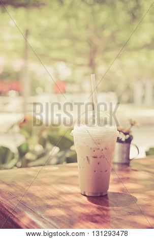 iced milk coffee in plastic cup on wooden table in tree background vintage style