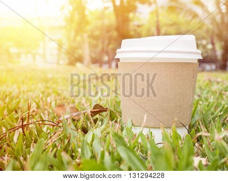 Closeup hot paper cup of coffee on grass in the garden at the morning with warm / soft color tone