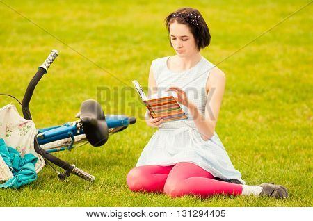 Pretty Young Woman With Book And Retro Bicycle Resting