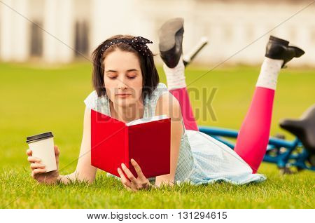 Nice Young Woman Reading A Book And Enjoying A Coffee