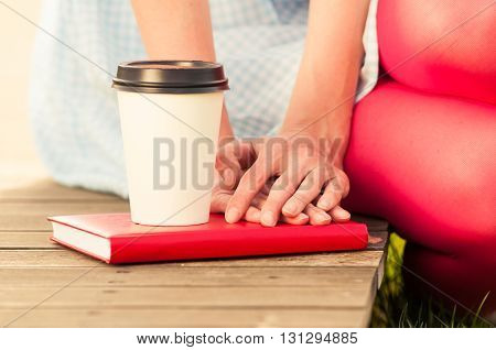 Close-up Of A Coffe And Woman Hands Hold On Book