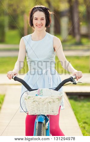 Portrait Of Joyful Female Riding A Bicycle In The Park