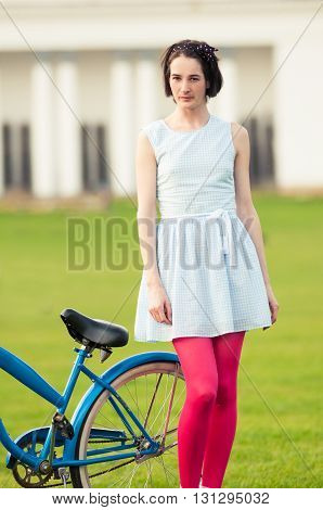 Young Hipster Female Standing Near Her Blue Retro Bicycle