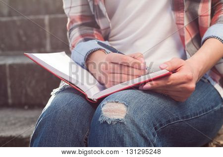 Close-up Of Woman Hand Writing On Notebook In The Park