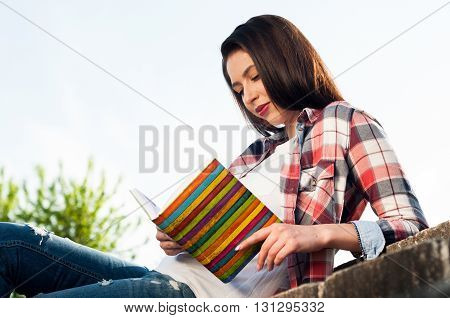 Portrait Of Young Hipster Female Reading Book In The Park