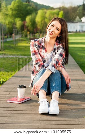 Beautiful Smiling Hipster Relaxing In Nature With Coffee And Book