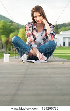 Relaxed Young Woman Reading A Book While Sitting Down