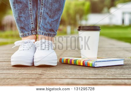 Close-up View Of Woman Legs Sitting On Wooden Alley