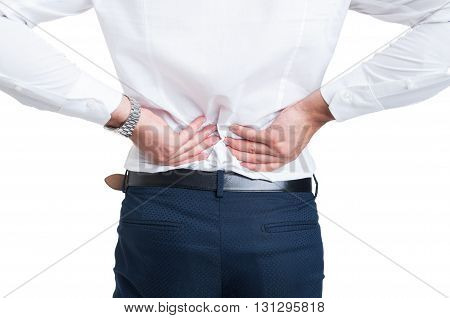 Backache concept with businessman in back view holding hands on lower back isolated on white background