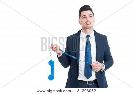 Pensive Businessman Holding An Old Blue Receiver And Thinking