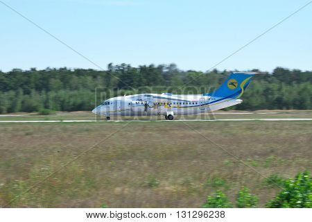 Kiev Region Ukraine - August 21 2012: Antonov An-148 regional passenger plane using jet thrust reverser on runway after landing