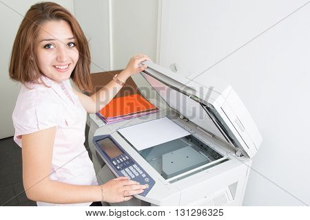 Cheerful Young Secretary Using A Copy Machine
