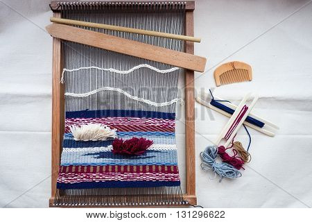 topview of tools and thread for weaving hand loom for weaving