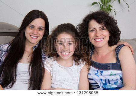 Proud smiling mother and her two girls at home