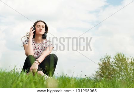 Enjoying Music Concept With Young Female Sitting Outside With Earphones