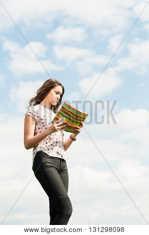 Attractive Young Girl Standing Outdoors And Reading A Book