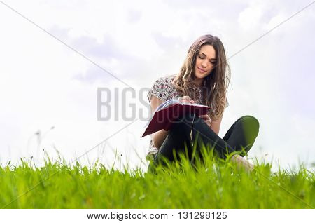 Beautiful Young Girl With A Notebook Siting Down On Lawn