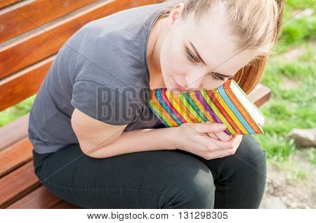 Young Attractive Female Holding Her Notebook And Relaxing On Bench