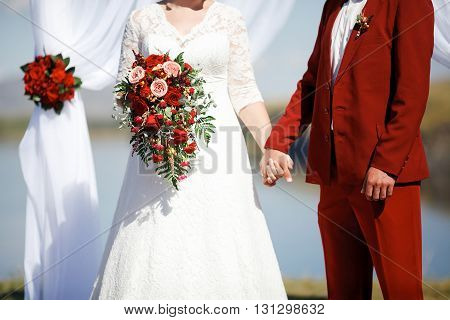Wedding in style Marsala color. Bride and groom holding hands at the altar in the arch background, chic wedding bouquet of roses in hands.