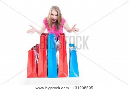 Cheerful shopaholic woman with many present or shopping bags smilling happily with copyspace isolated in white