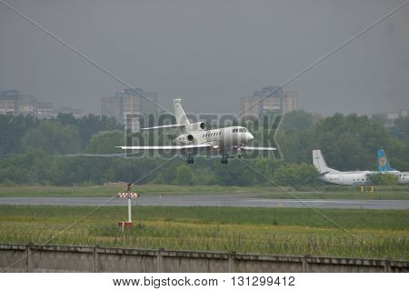 Kiev UKraine - June 5 2012: Dassault Falcon 50EX business jet is landing in bad weather conditions under heavy rain