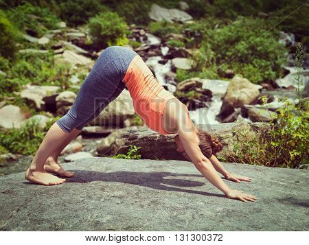 Vintage retro effect hipster style image of sporty fit woman doing yoga asana Adho mukha svanasana - downward facing dog - at tropical waterfall