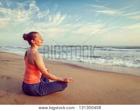 Vintage retro effect hipster style image of woman doing yoga - meditating and relaxing in Padmasana Lotus Pose) with chin mudra outdoors at tropical beach on sunset