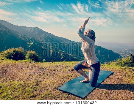 Vintage retro effect hipster style image of woman doing Ashtanga Vinyasa yoga advanced difficult asana Vatayanasana (Horse pose) outdoors in Himalayas mountains. Himachal Pradesh, India