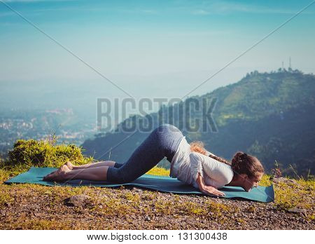 Vintage retro effect hipster style image of woman doing yoga asana Ashtangasana eight-limbed pose outdoors in mountains in the morning in Himalayas