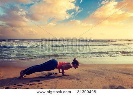 Vintage retro effect hipster style image of woman practices Ashtanga Vinyasa yoga Surya Namaskar Sun Salutation asana Chaturanga Dandasana - four-limbed staff pose at the beach on sunset