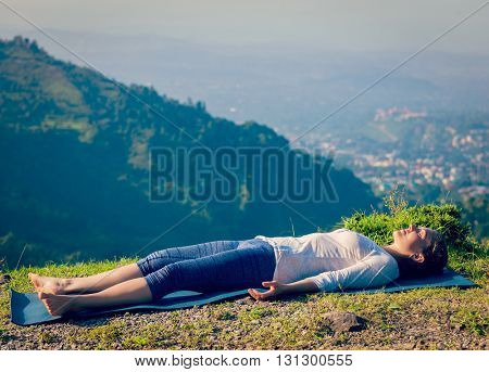 Vintage retro effect hipster style image of woman relaxes in yoga asana Savasana - corpse pose outdoors in Himalayas. Himachal Pradesh, India